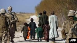U.S. Marines escort farmers fleeing their land as Marines battle Taliban in Trikh Nawar, near Marjah.