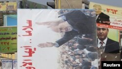 Residents remove a campaign billboard from a street in Baghdad on March 8, one day after the voting.