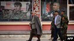 FILE: Afghan Vice President Abdul Rashid Dostum (L) walks at his headquarters in Sheberghan, capital of northern Jowzjan province on July 28.