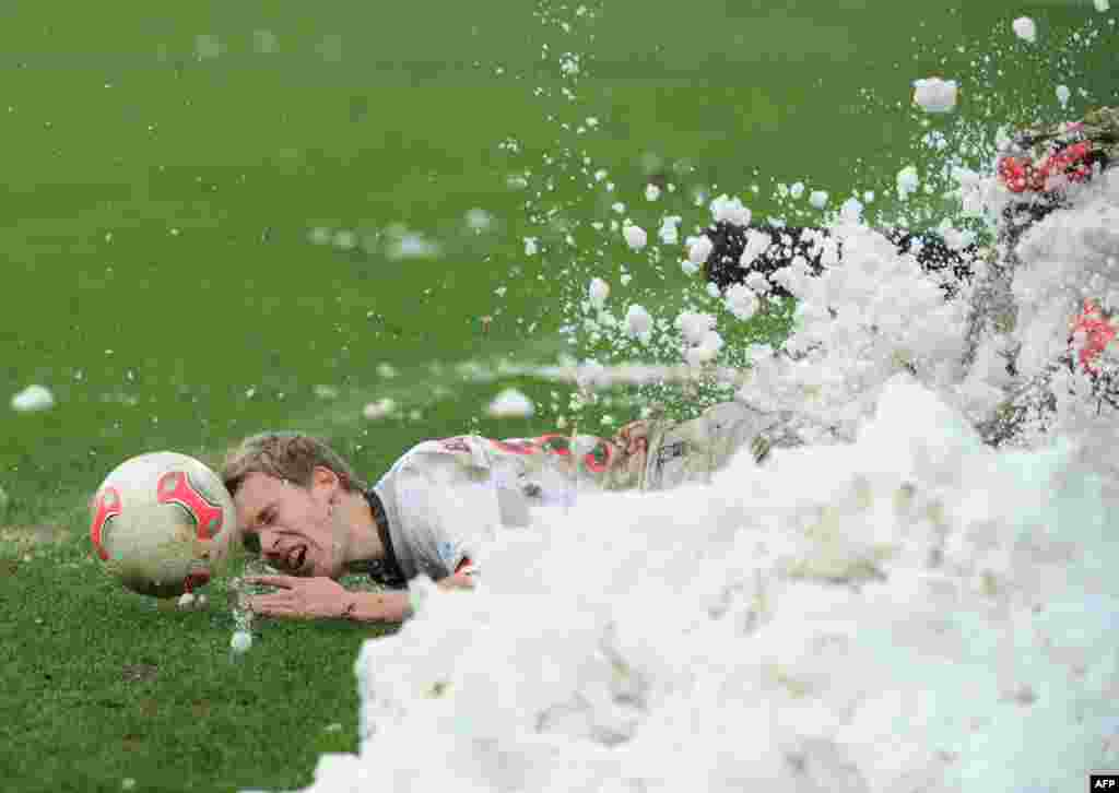 St. Pauli's Christopher Buchtmann slides into a heap of snow during a Bundesliga match between FC St. Pauli and Erzgebirge Aue at Millerntor-Stadion in Hamburg, Germany. (AFP/Angelika Warmuth)