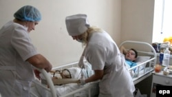 врачи с подростком, раненным во время обстрела школы под Донецком, 6 ноября 2014 года.