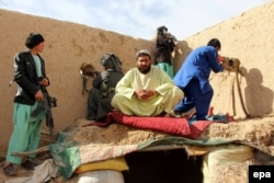 Afghan Local Police (ALP) take positions during an operation against Taliban militants in Sangin on January 31