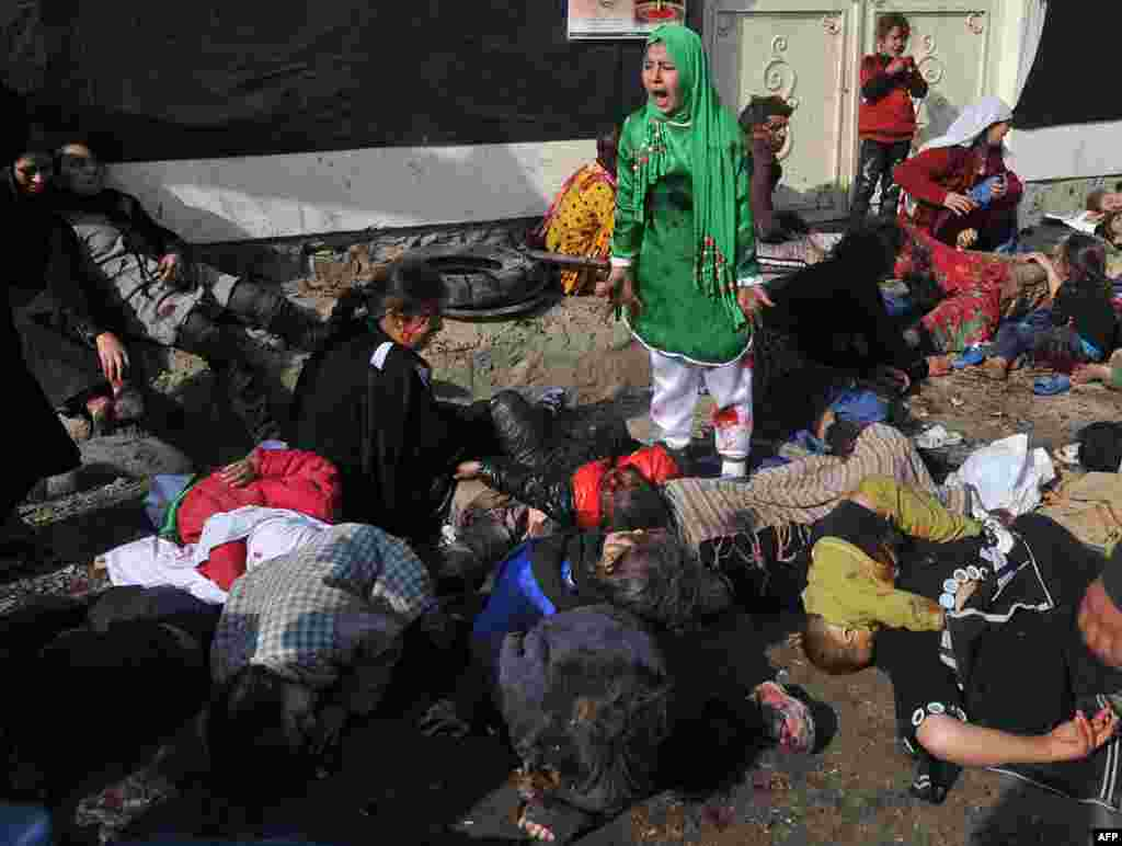 The photograph that was awarded the Pulitzer Prize, showing Tarana Akbari reacting amid the casualties after the suicide bombing at a crowded Shi'ite shrine in Kabul on December 6, 2011.