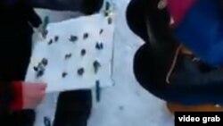 Құмалақшыға ер адамның доқ көрсеткені жайлы видеодан скриншот.