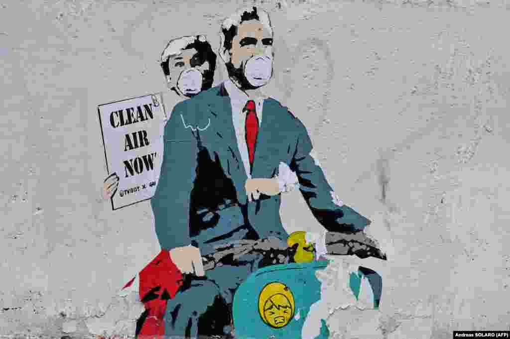 """A mural near theColosseum in central Rome by Italian street artist TV Boy depicts a scene from the famous film Roman Holiday. Mask-wearing Gregory Peck and Audrey Hepburn hold a sign that says """"Clear Air Now."""""""