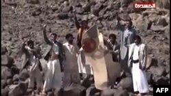 Йемендик уруунун адамдары истребителдин Марокконун желеги тартылган сыныгын кармап турушат. Вади Нушур району, 11-май 2015