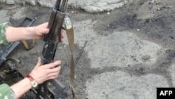 Ukraine -- A pro-Russian militant examines damaged Kalashnikov rifles on 04Jun2014
