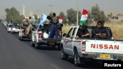 A military convoy drives towards Kirkuk, to reinforce Kurdish troops in Kirkuk on June 24.