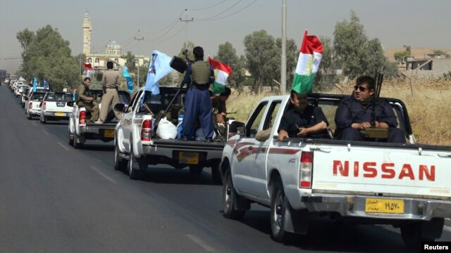 A military convoy drives towards Kirkuk, to reinforce Kurdish troops in Kirkuk on June 24.