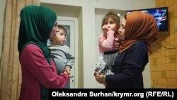 Аліє Емірусеїнова та Азізе Абхаїрова з дітьми Абхаїрових на руках