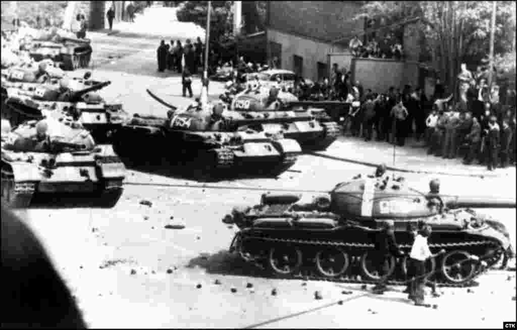 Protesters throw stones at the Soviet tanks entering Prague.