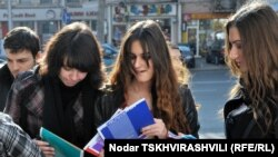Representatives of Transparency International distribute copies of the corruption report to students in Tbilisi as part of Anticorruption Day activities.