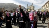IFILE: Afghan protestor wear masks during a protest to condemn the killing of 27-year-old woman, Farkhunda, who was lynched after a healer allegedly incited a mob in Kabul in 2015.