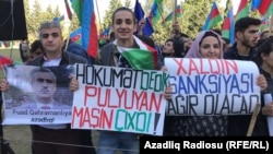 Opposition activists with signs at Baku demonstration