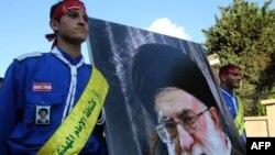 دو جوان در حال حمل عکس رهبر ایران در جریان مراسم خاکسپاری یکی از اعضای گروه حزب الله لبنان (عکس از آرشیو)