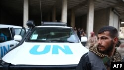 Сириец рядом с автомобилем ООН, сопровождающий гуманитарную помощь Красного Полумесяца в район Кафр Батна, удерживаемом повстанцами. Дамаск, 23 февраля 2016 года.