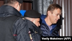 Russian police officers detain opposition leader Aleksei Navalny outside the detention center in Moscow on the morning of September 24.