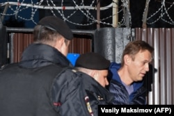 Russian police officers detain opposition leader Aleksei Navalny upon his release from a Moscow detention center on September 24.