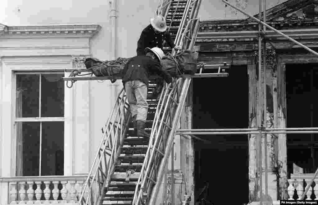 Firefighters remove one of the bodies found in the charred remains of the embassy on May 7, 1980. The corpse, wrapped in a dark green body bag, was lowered from a second-floor front window.