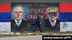 A woman walks past a mural depicting Russian President Vladimir Putin and U.S. President Donald Trump in Belgrade.
