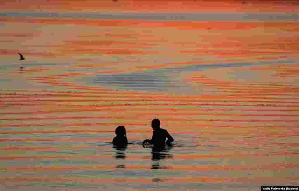 Bathers enjoy the sunset in a lake on the outskirts of Minsk, Belarus. (Reuters/Vasily Fedosenko)