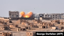Smoke rises from buildings in the area of Bughayliyah, on the northern outskirts of Deir al-Zor on September 13.