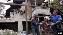 Russian Emergency Ministry officers help an elderly Georgian woman leave her destroyed home in the South Ossetian village of Kurta on August 20, 2008.