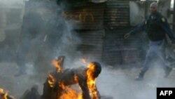 پلیس آفریقای جنوبی به کمک مردی می آید که به آتش کشیده شده است. (عکس:AFP)