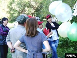 Организаторы фотоконкурса развешивают на деревьях шары и фотографии участников. Талдыкорган, 24 июня 2010 года.