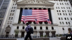 U.S. -- A pedestrian walks past the New York Stock Exchange on earl in New York, 05Aug2011