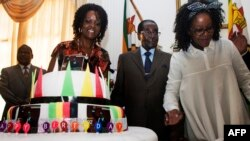 Zimbabve prezidenti Robert Mugabe (ortada) və birinci ledi Grace Mugabe (solda)