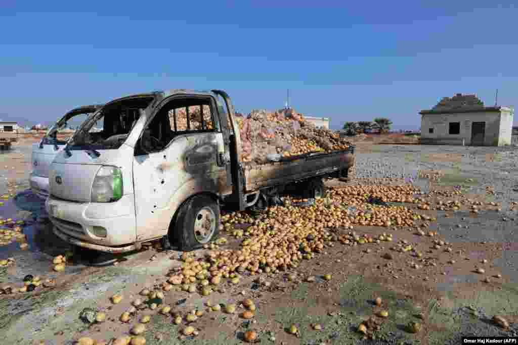 Small trucks loaded with potatoes stand abandoned following air strikes by government forces that hit a vegetable market in the town of Saraqeb in Syria's northwestern province of Idlib. (AFP/Omar Haj Kadour)