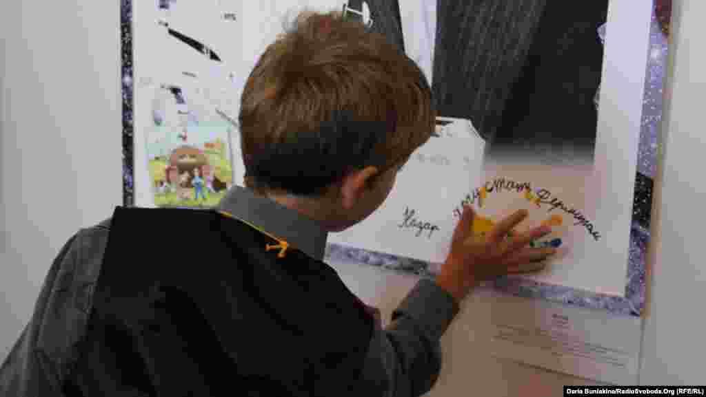 10-річний Назар підписує свій фотопортрет