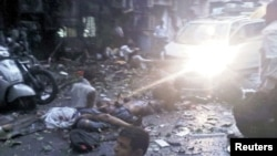 Injured people lie in the street at the site of the explosion