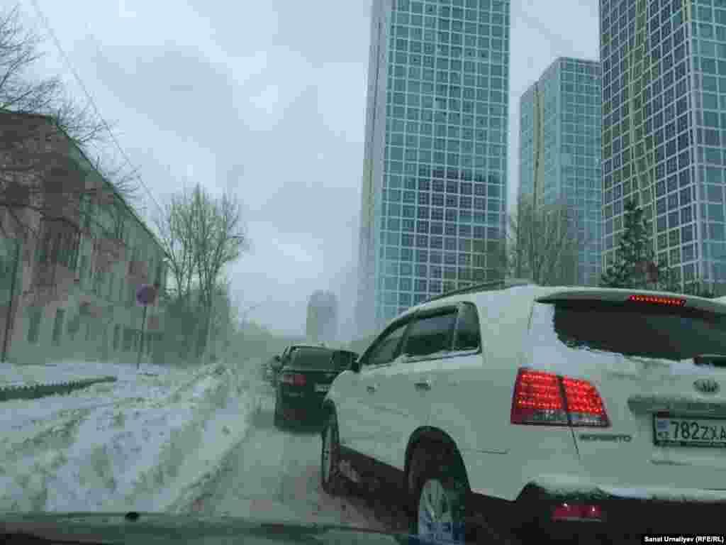 На заснеженных улицах в старом центре города, на правом берегу, часто образуются заторы. Нур-Султан, 28 января 2020 года.