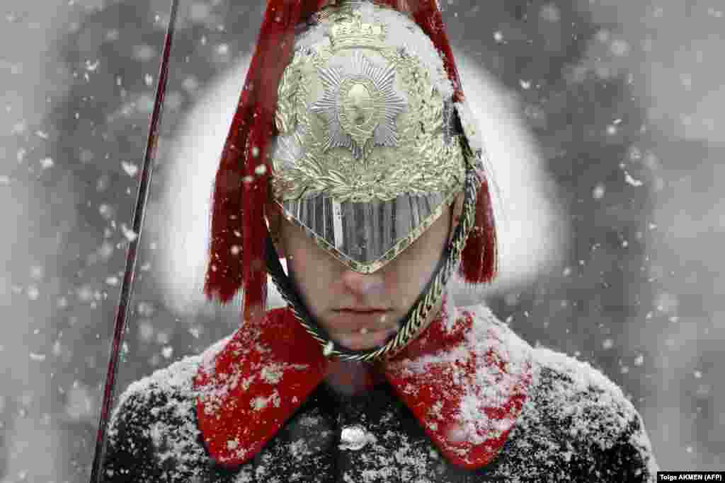 Snow falls on a member of the Household Cavalry Mounted Regiment on Whitehall in central London. (AFP/Tolga Akmen)