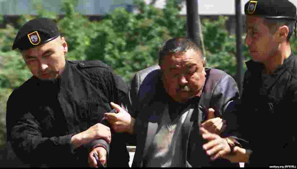 """Попытки провести протесты """"по земельному вопросу"""" предпринимались в Алматы и до 21 мая 2016 года, за несколько недель до этой даты. Однако немногочисленных активистов, приходивших на центральную площадь, тотчас же задерживали. На фото: полиция задерживает мужчину рядом с монументом Независимости 7 мая 2016 года."""
