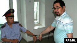 A police officer leads opposition activist Yermek Narymbaev to court in handcuffs.