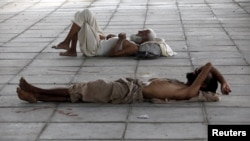Men sleep in the shade under a bridge during intense hot weather in Karachi on June 22.