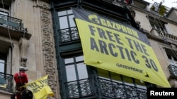 Greenpeace activists in Paris demonstrate in support of their colleagues in custody in Russia on October 9.