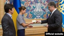 Ukrainian President Petro Poroshenko (right) gives Ukrainian citizenship to Russian public figure Maria Gaidar (center) in Kyiv on August 4.