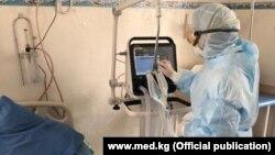 Медработник в защитной одежде у аппарата искусственной вентиляции легких.