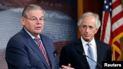 U.S. Senate Foreign Relations Committee Chairman Robert Menendez (left) and Senator Bob Corker speak to reporters after a Senate vote on an aid package for Ukraine, in Washington on March 27, 2014.