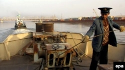Uzbekistan -- a barge being pulled on the Amu Darya river towards the Uzbek 'Friendship Bridge', seen in background, connecting the Uzbek border town of Termez with the Afghan city of Heiraton 21Nov2001