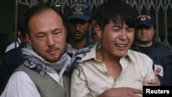 A relative of one of the shooting victims is comforted at the local hospital in Quetta.