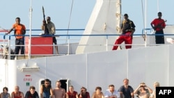 "Pirates stand guard over the crew of the hijacked Ukrainian merchant ship ""MV Faina"" in November."