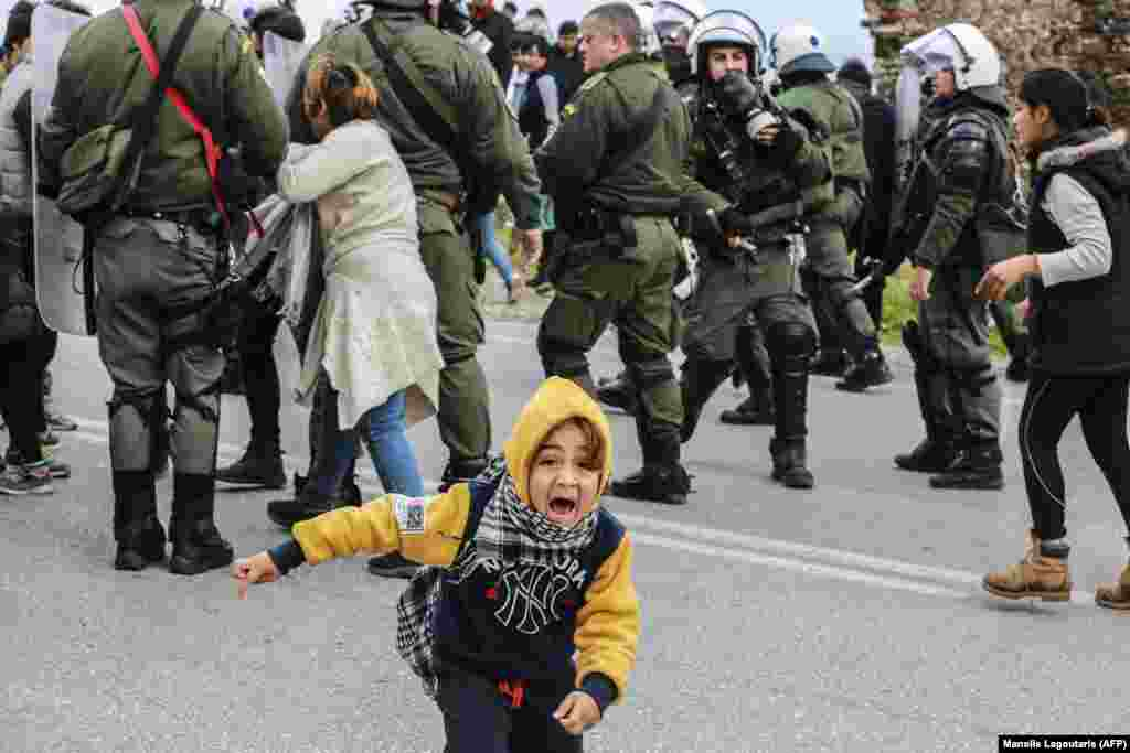 A young migrant reacts during clashes with riot police as refugees and migrants demonstrated against a new law tightening asylum procedures in Greece, outside the Kara Tepe camp on the island of Lesbos. (AFP/Manolis Lagoutaris)