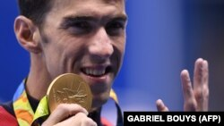 USA's Michael Phelps holds up four fingers for his fourth gold medal on the podium of the Men's 200m Individual Medley Final during the swimming event at the Rio 2016 Olympic Games at the Olympic Aquatics Stadium in Rio de Janeiro on August 11, 2016.