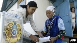 Член избирательной комиссии помогает пожилой женщине с бюллетенем во время парламентских выборов в Бес-Агаше. 18 августа 2007 года.