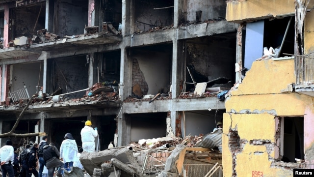 Police forensic experts examine a destroyed police station in Cinar in the southeastern city of Diyarbakir on January 14.